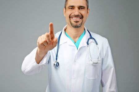 Portrait of a doctor with stethoscope on grey background