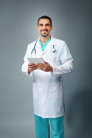 Portrait of a doctor with tablet in hands on grey background