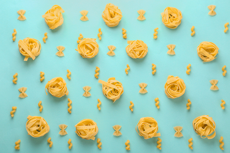 Flat lay composition with different uncooked pasta on color background Stock Photo