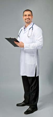 Portrait of a doctor with prescription board in hands on grey background Reklamní fotografie