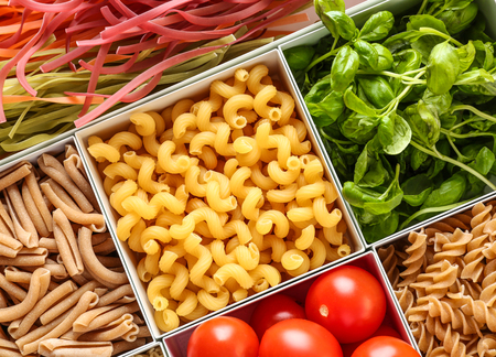 Boxes with different uncooked pasta and products, closeup