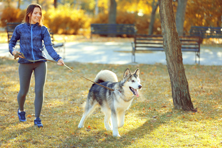 Happy young woman walking with her dog in park Stock Photo