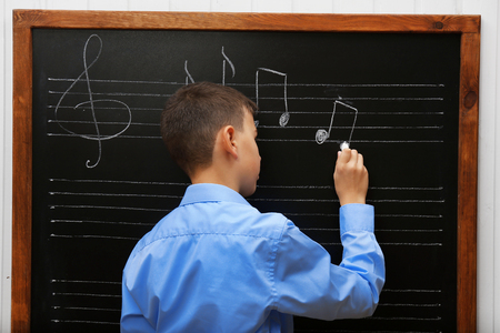 Young cute schoolboy writing at the blackboard Stock Photo