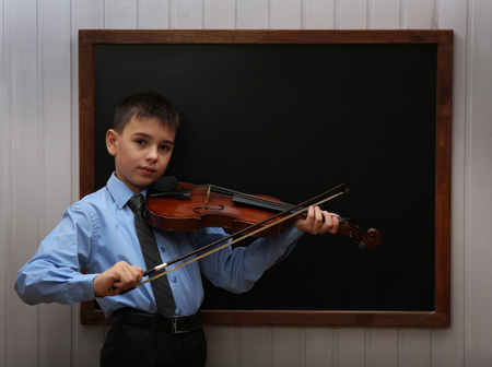 Young cute schoolboy playing the violin at the blackboard