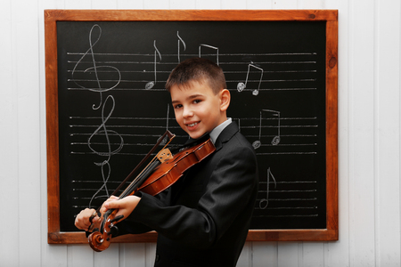 Young cute schoolboy playing the violin the blackboard with musical notes Stock Photo