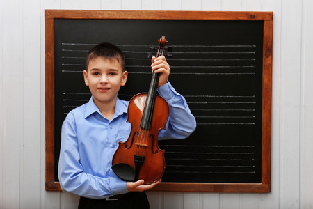 Young cute schoolboy holding the violin at the blackboard Stock Photo