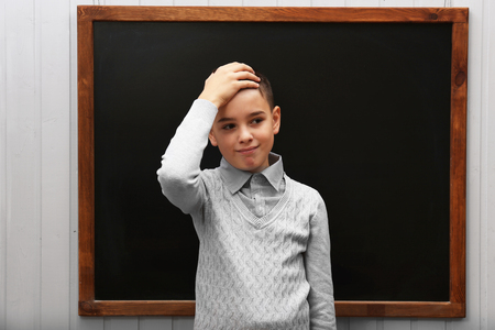 Young cute schoolboy posing at the blackboard Stock Photo