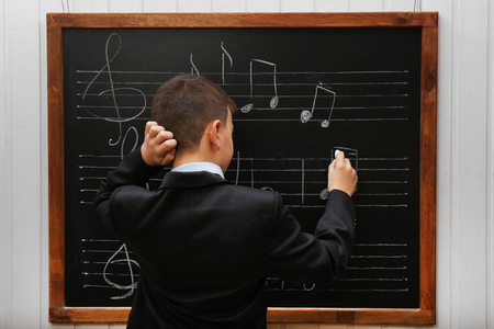 Young cute schoolboy standing at the blackboard with musical notes Stock Photo