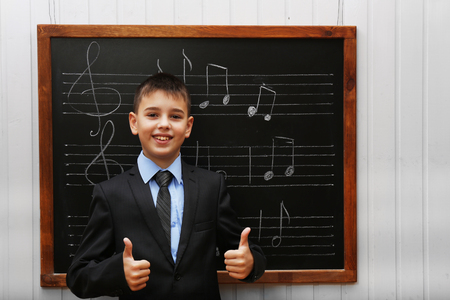 Young cute schoolboy standing at the blackboard with musical notes Stockfoto