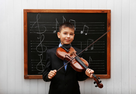 Young cute schoolboy holding the violin at the blackboard with musical notes Stock Photo