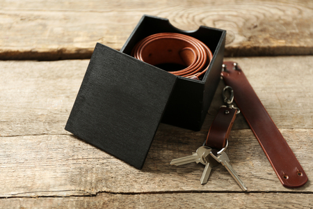 Leather belt with buckle in gift box on wooden background 写真素材