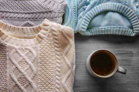 Mug of tea and warm clothes on wooden background Stock Photo