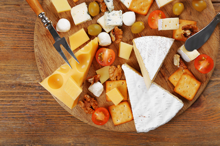 Cheese for tasting on wooden background, top view Stock Photo