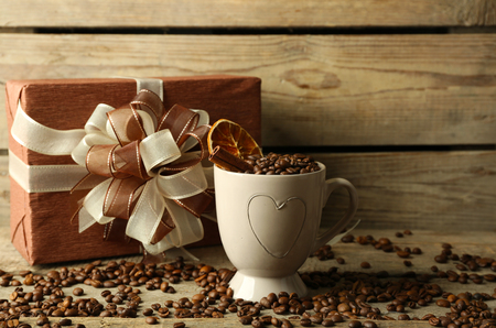 Beautiful gift with bow and coffee grains in mug, on wooden background Banco de Imagens