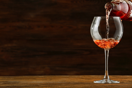 Rose wine pouring in glass on wooden background Фото со стока
