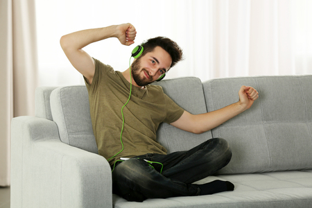 Young man listens music with headphones sitting on grey sofa in the room Фото со стока