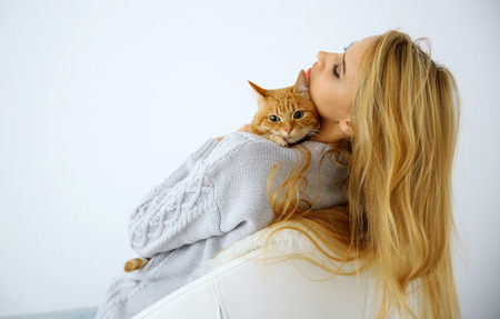 Young woman with red cat sitting on chair against white background, close up