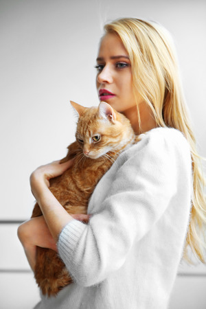 Young woman holds red cat in hands, close up Stock Photo