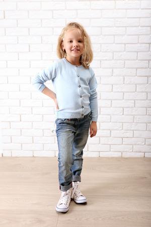 Little girl on a white brick wall background Archivio Fotografico