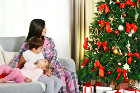 Mother with daughter and son near Christmas tree