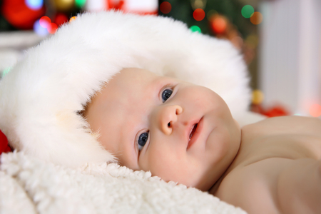 Cute naked baby in red hat on the warm blanket, close up