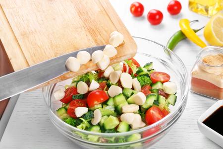 Adding mozzarella cheese to salad, at kitchen Stock Photo