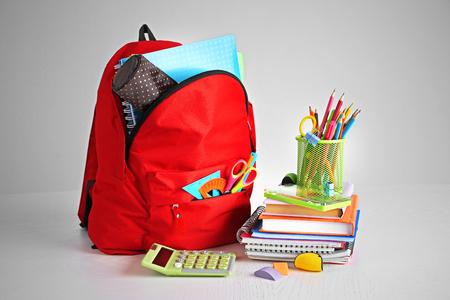 Sac à dos avec fournitures scolaires sur table en bois