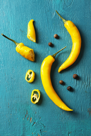Yellow chili peppers on color wooden background