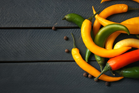 Yellow chili peppers on wooden background