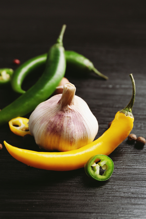 Garlic, green and yellow chili peppers on dark wooden background