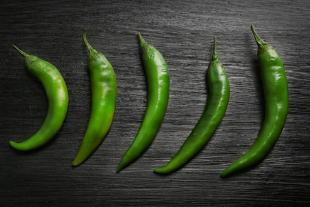Green chili peppers on dark wooden background