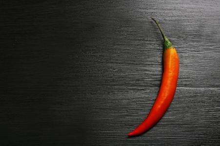 Red chili pepper on dark wooden background