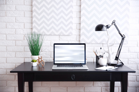 Workplace with laptop on table at home