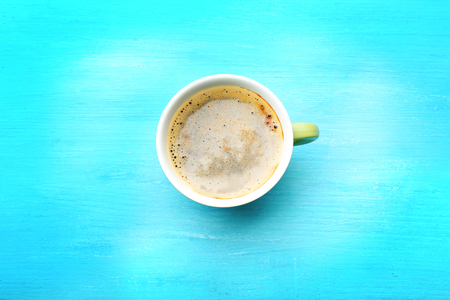 Cup of coffee on turquoise background, top view Foto de archivo