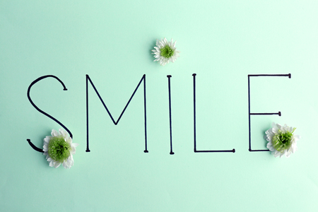 Inscription smile with white flowers on green background