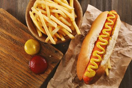 Hot dog with fried potatoes on craft paper closeup Standard-Bild