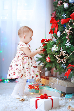 Funny baby girl decorating Christmas tree on bright background Stock Photo