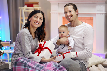 Happy family with gifts against decorated fireplace in the room