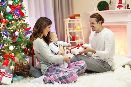 Happy parents with baby near Christmas tree on the floor in the decorated room
