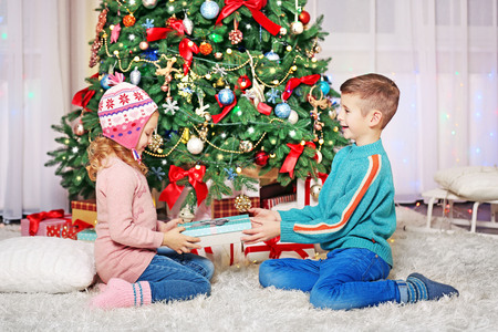 Happy children with gifts in the decorated Christmas room