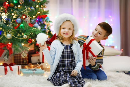 Happy children playing with gifts in the decorated Christmas room Stock Photo