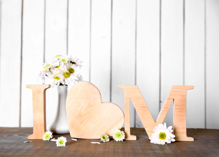 Wooden letters with heart and flowers on white wall background Stock Photo