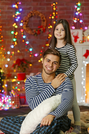 Happy older brother with little sister in Christmas living room Stockfoto