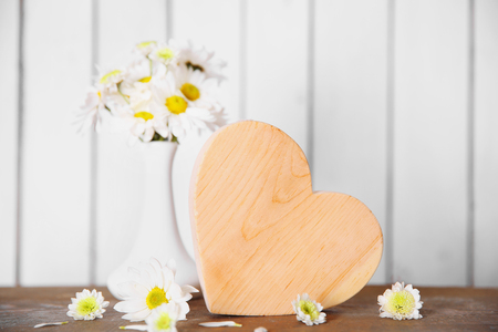Wooden heart with flowers on a white wall background 版權商用圖片