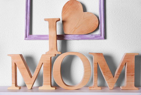 I love mom inscription of wooden letters with heart on white wall background Stock Photo