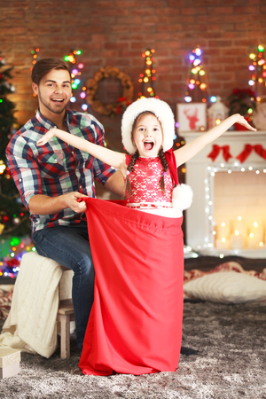 Funny little sister in Santa sack surprising her older brother on Christmas background Foto de archivo