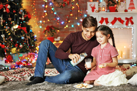 Older brother and little sister drinking milk with cookies in Christmas living room