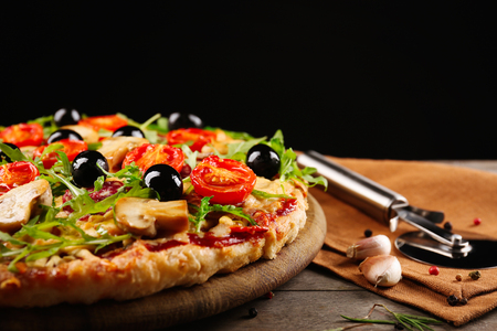 Delicious tasty pizza with cutter on black background