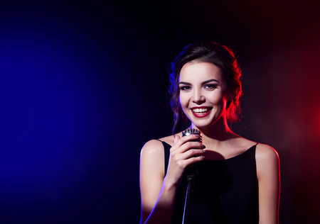 Portrait of beautiful singing woman on dark background Stock Photo