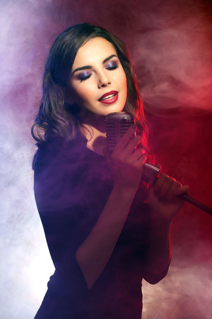 Beautiful singing woman on red background in the smoke, close up
